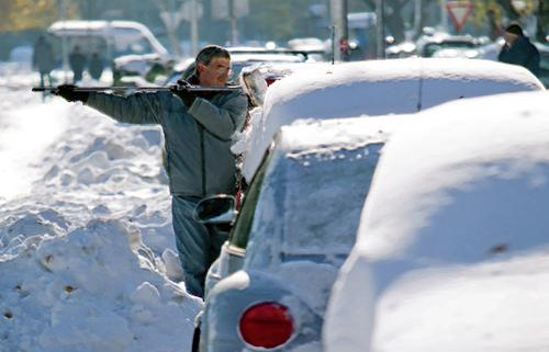 Мужчина ждёт прогрева двигателя и очищает от снега автомобиль
