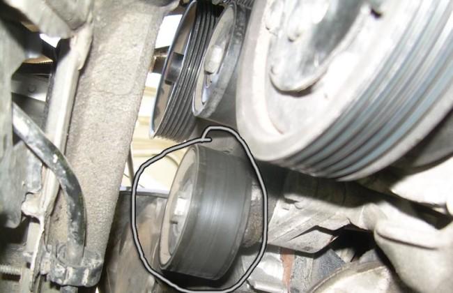 Ролик натяжителя ремня генератора под капотом Рено Логан