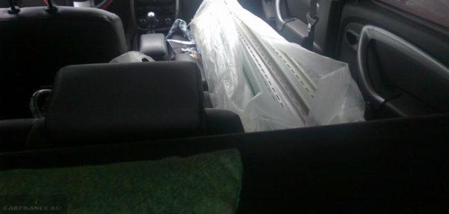 Спинка заднего сидения опущена на половину Рено Дастер