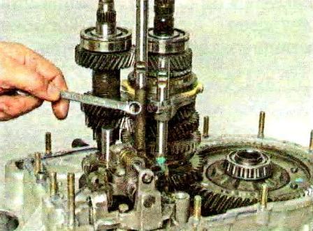 Отверткой выводим рычаг штока из зацепления в механизме переключения передач КПП