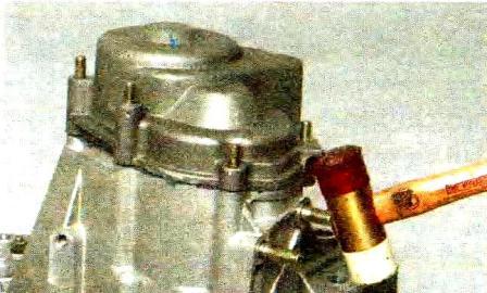 Постукивая молотком с пластмассовым наконечником или обычным молотком через оправку из мягкого металла по приливам крышки КПП Лада Гранта