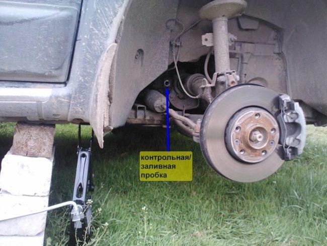 Снятое переднее колесо с указанием контрольной точки заливной пробки на Рено Дастер