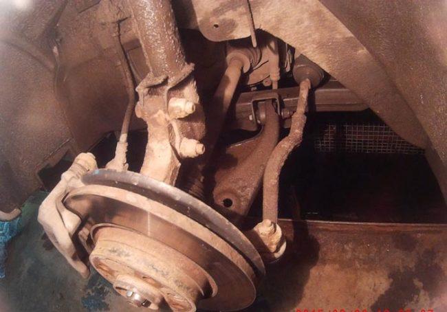Сняли колёса виден рычаг подвески Рено Логан