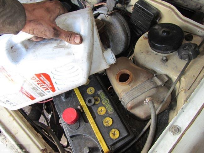Бутылка с охлаждающей жидкостью и расширительный бачок под капотом ВАЗ-2114 крупным планом