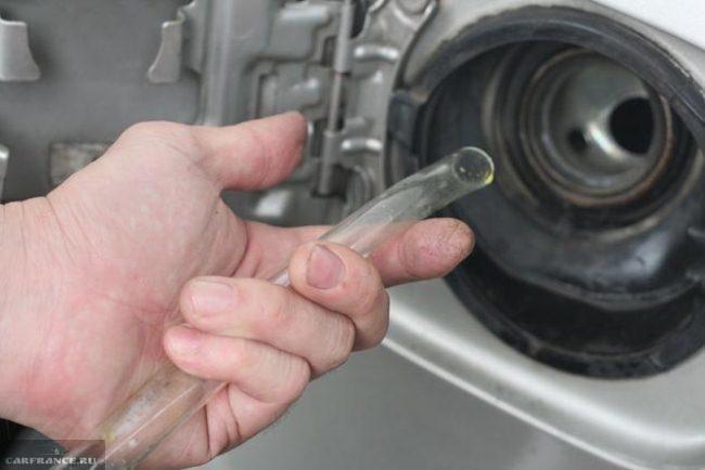 Открытый бензобак ВАЗ-2114 и шланг в руках крупным планом