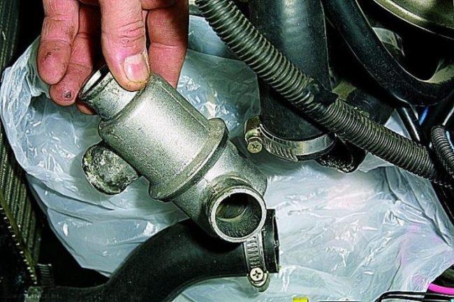 Демонтированный термостат ВАЗ-2114 с патрубками вблизи