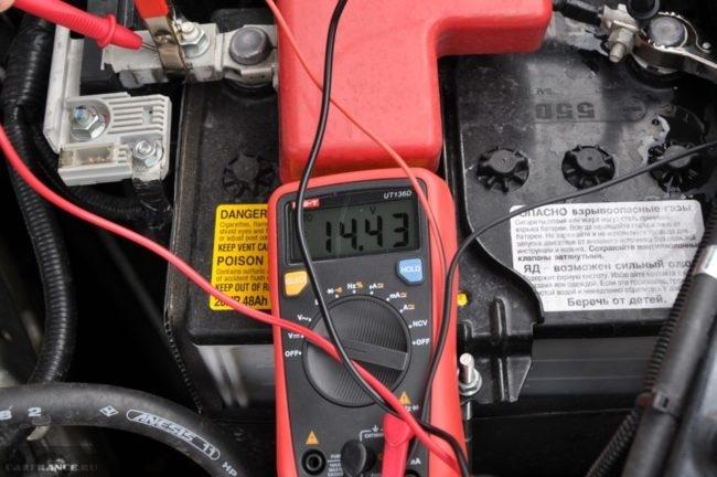 Проверка напряжения на клеммах аккумулятора с помощью мультиметра при заведённом моторе