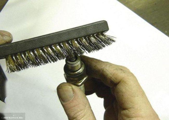 Процесс очистки электродов свечи зажигания ВАЗ-2114 от нагара щеткой