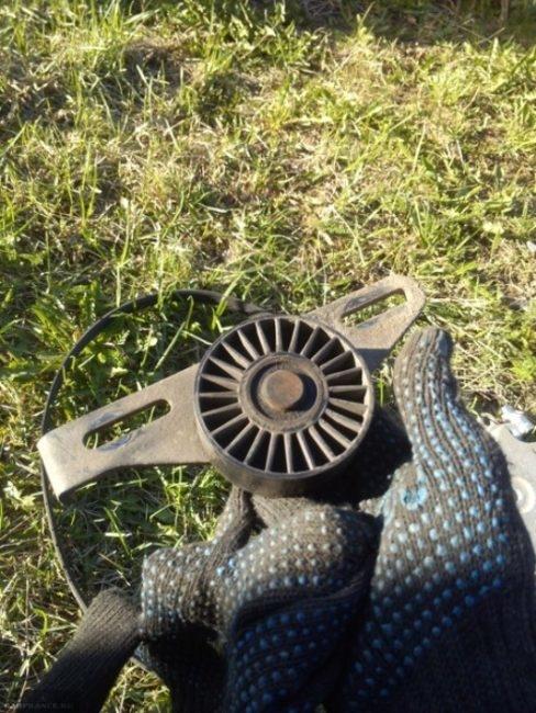 Старый ролик натяжения ремня генератора Рено Симбол вблизи
