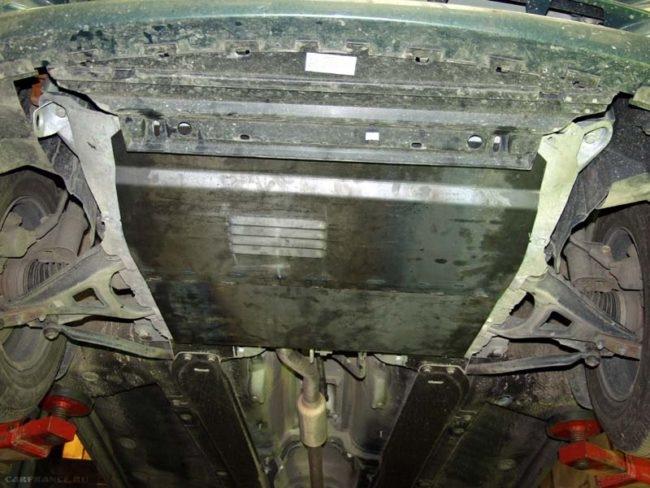 Процесс демонтажа защитного кожуха картера Рено Симбол, вид из-под машины