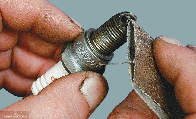 Процесс очистки электродов свечи зажигания наждачной бумагой