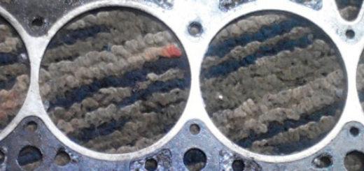 Прогоревшая прокладка головки блока цилиндров двигателя вблизи