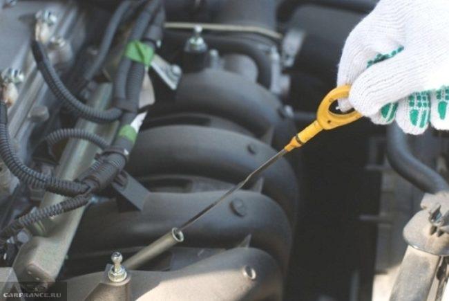 Процесс проверки уровня масла в двигателе с помощью щупа