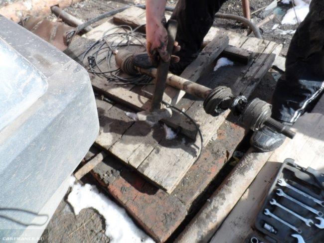 Процесс демонтажа наружного шруса Нива Шевроле при помощи молотка и наставки