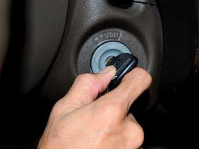 Человек прокручивает ключ в замке зажигания автомобиля