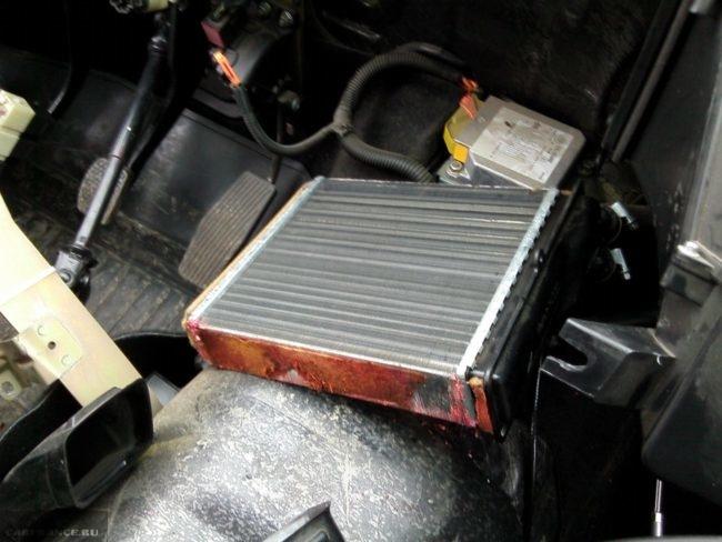 Демонтированный старый радиатор отопителя в салоне Нива Шевроле