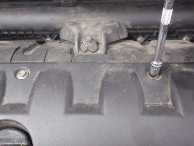 Процесс откручивания болтов крепления декоративной крышки од капотом Пежо 308