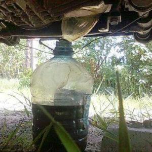 Старое масло стикает из двигателя в бутылку на Шевроле Нива