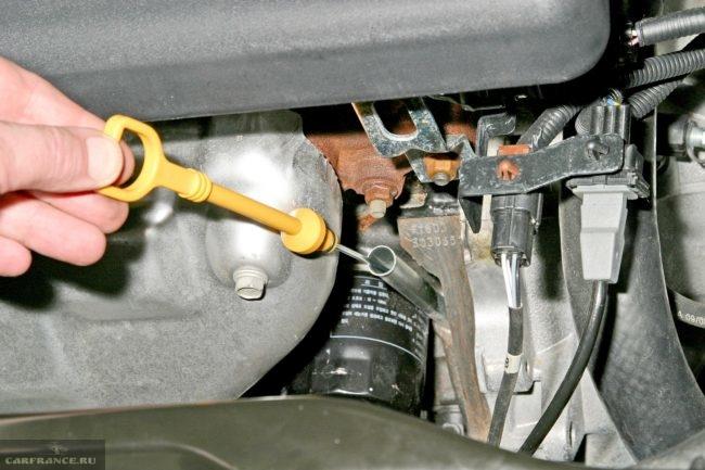 Процесс проверки уровня масла щупом в двигателе Шевроле Лачетти