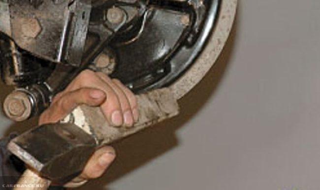 Демонтаж тормозного барабана Нива Шевроле с помощью молотка и деревянной проставки