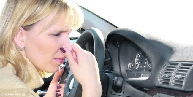 Девушка в салоне Пежо Партнер закрывает нос из-за неприятного запаха