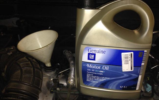 Моторное масло и лейка для замены в двигателе на Шевроле Каптива