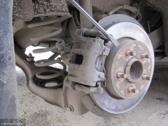 Демонтаж пружины на механизме задних тормозных колодок Форд Фокус 2