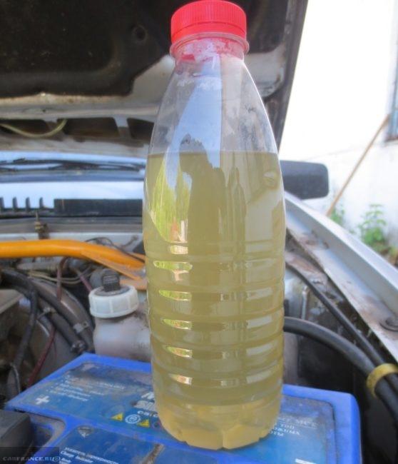 Бутылка с промывочной жидкостью, слитой из радиатора ВАЗ-2110