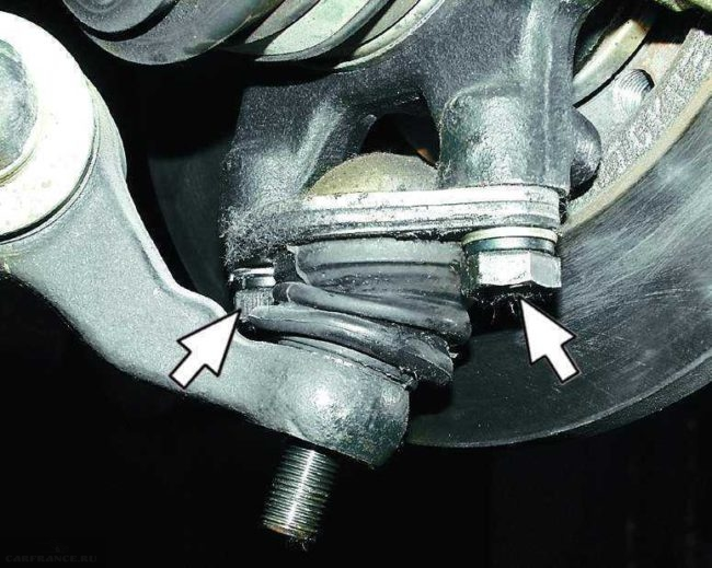 Шаровая опора на автомобиле ВАЗ-2110 без гайки крепления к рычагу подвески, стрелками показаны болты и шайбы крепления к поворотному кулаку
