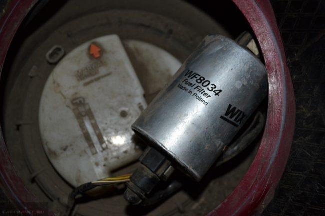 Топливный фильтр над бензобаком автомобиля Пежо 307, вид со снятым лючком