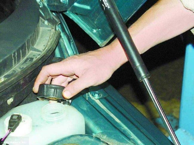 Расширительный бачок охлаждающей жидкости в автомобиле ВАЗ-2110 и крышка в руке