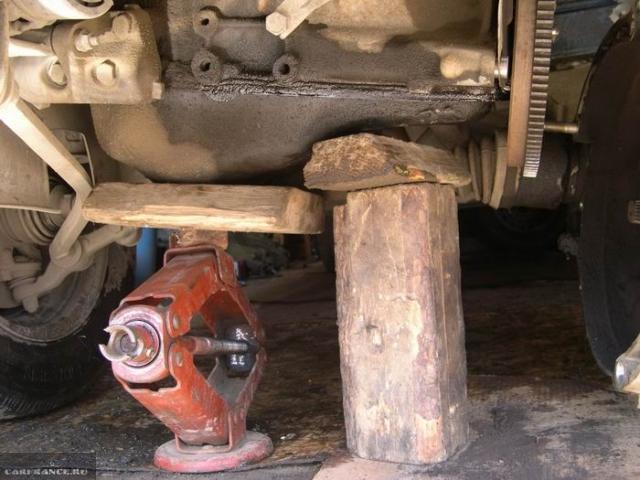Двигатель автомобиля ВАЗ-2110 на деревянной опоре, вид снизу, коробка передач снята с креплений