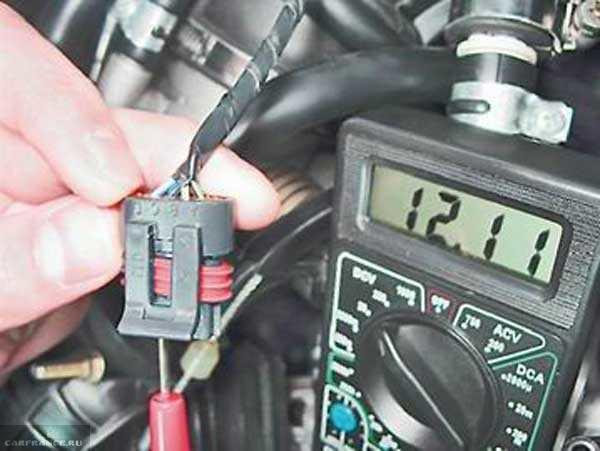 Соединительная колодка датчика холостого хода в ВАЗ-2110 и мультиметр, замер напряжения питания