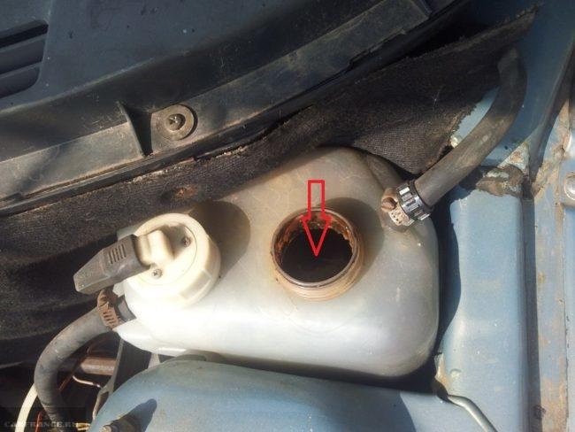 Расширительный бачок системы охлаждения двигателя ВАЗ-2110, виден тосол темного цвета