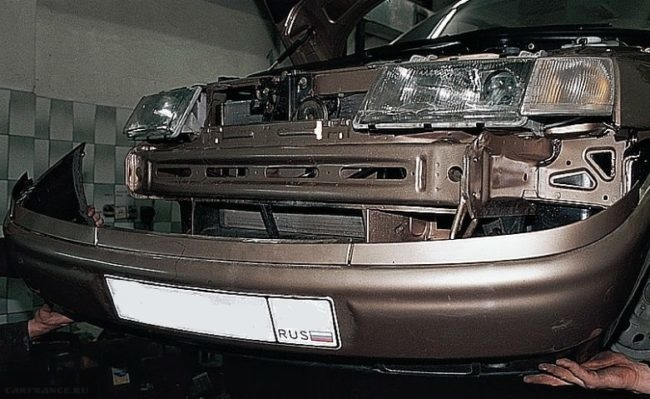 Передний бампер автомобиля ВАЗ-2110 отведен от кузова и удерживается на руках