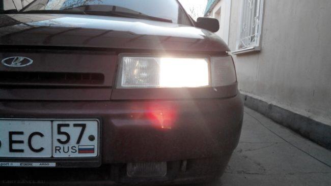 Передняя фара автомобиля ВАЗ-2110 вблизи, горит лампа ближнего света