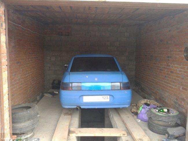 Автомобиль ВАЗ-2110 на смотровой яме в гараже, ворота открыты
