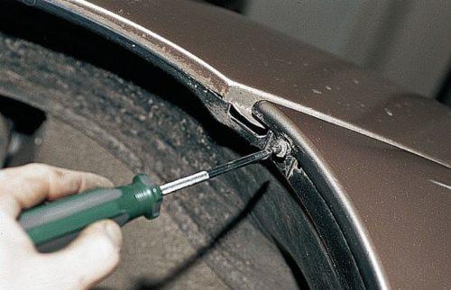 Винт верхнего крепления подкрылка к переднему бамперу в ВАЗ-2110 и отвертка с крестообразным наконечником