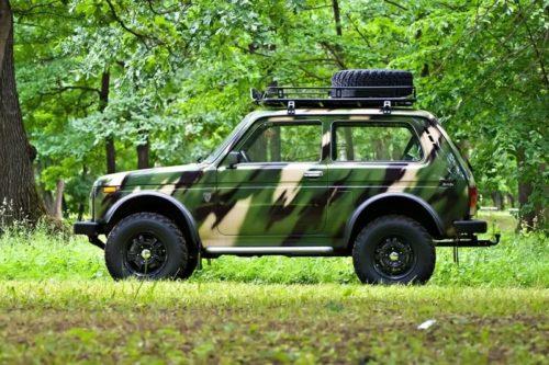 Автомобиль Лада 4х4 2018 года в комплектации Камуфляж на фоне деревьев