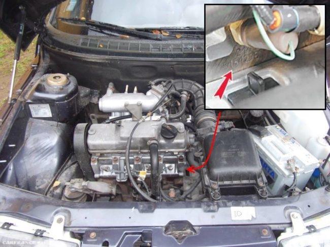 Моторный отсек автомобиля ВАЗ-2110 с поднятым капотом и указанием месторасположения номера двигателя