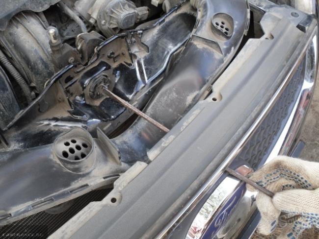 Процесс вскрытия замка капота Форд Фокус 2 длинной плоской отверткой
