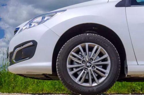 Переднее колеса с литым диском на белом седане Пежо 408 2018 года