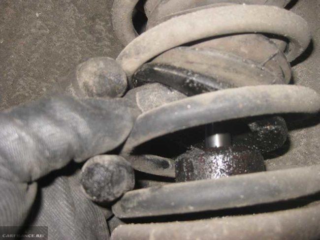 Потеки масла на штоке амортизатора передней стойки ВАЗ-2110, вид с приподнятым пыльником