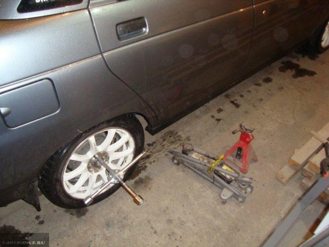 Заднее правое колесо автомобиля ВАЗ-2110, домкрат и трехногая подпорка