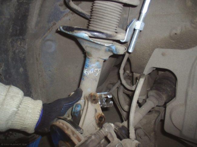 Передняя стойка ВАЗ-2110 в процессе демонтажа для последующей замены