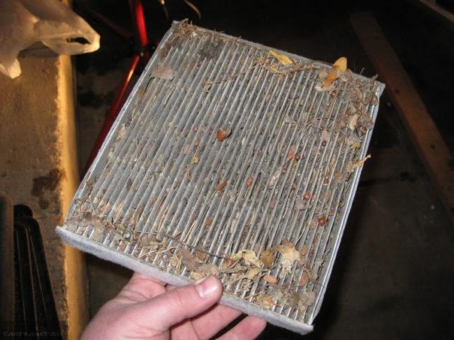 Грязный и забитый листьями салонный фильтр из автомобиля ВАЗ-2110
