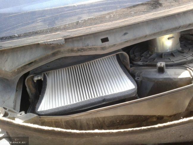 Новый фильтр салона с белыми гофрами в кожухе под ветровым стеклом автомобиля ВАЗ-2110