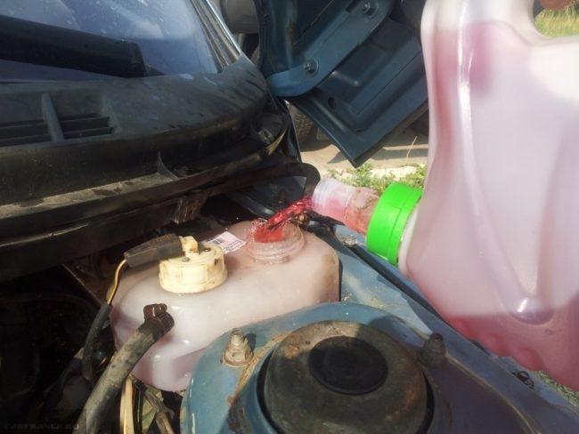 Заливка красной охлаждающей жидкости в расширительный бачок автомобиля ВАЗ-2110