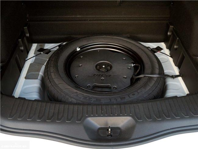 Запасное колесо и усилитель звука в багажнике кроссовера Рено Колеос 2018 года