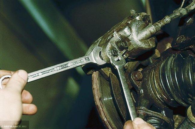 Процесс откручивания болта крепления супорта ВАЗ-2110